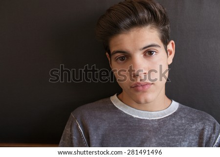Close up portrait of a young teenager man looking at camera with an insecure expression, against a dark background at home, interior. Teenager relaxing at home being serene and thoughtful, indoors. - stock photo