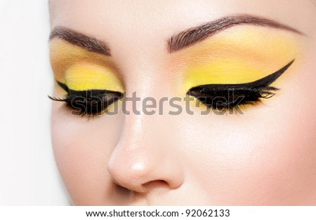 Close-up portrait of a young woman. Beautiful cat-eyeliner makeup. - stock photo