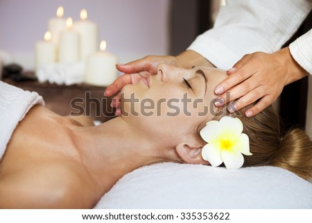Close up portrait of a young woman getting spa treatment. Face massage - stock photo