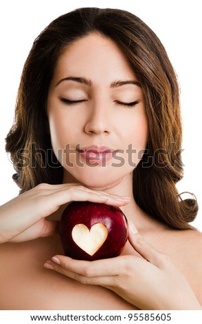 Close up portrait of a young woman holding red apple with heart shape - stock photo