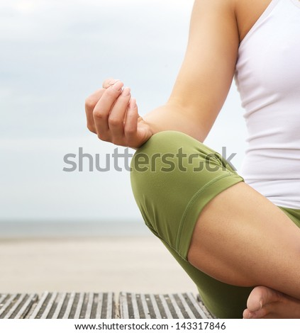 Close up portrait of a young woman in lotus position with yoga hands at the beach - stock photo