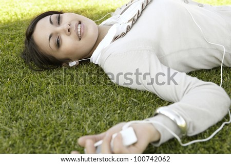 Close up portrait of a  young woman listening to music on her mp4, laying down on green grass in a park. - stock photo