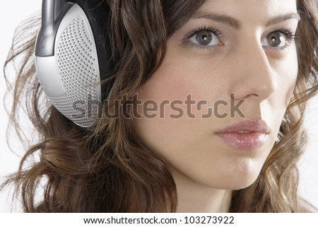 Close up portrait of a young woman listening to music with her headphones. - stock photo