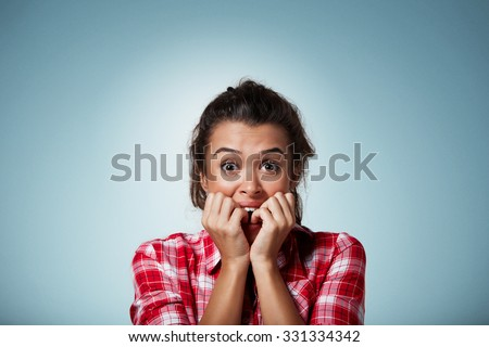 Close-up portrait of a young woman scared ,afraid and anxious biting her finger nails, looking at camera with wide opened eyes isolated on a blue background. Human emotions - stock photo