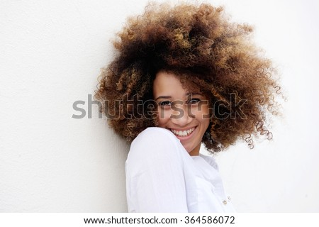 Close up portrait of a young woman smiling with afro hair against white background  - stock photo