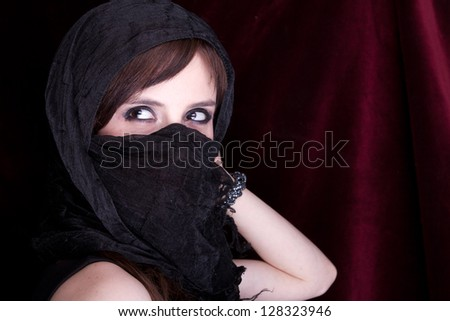 Close up portrait of a young woman wearing a head scarf and smiling at the camera, studio shot - stock photo