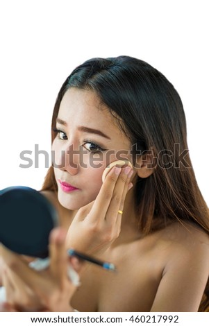 Close up portrait of a young woman with long hair on white background making beauty face and hair style, applying powder at face.