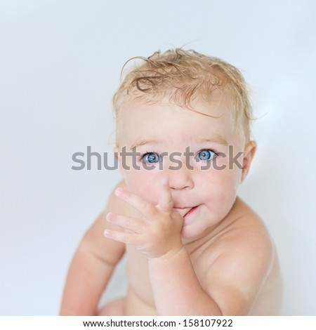 Close up portrait of adorable little baby girl sitting in a bath sucking on her thumb - stock photo