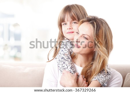 Close-up portrait of adorable little girl hugging her mother while sitting on sofa at home.  - stock photo