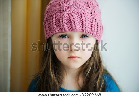 Close-up portrait of adorable sad child girl wearing pink knitted hat