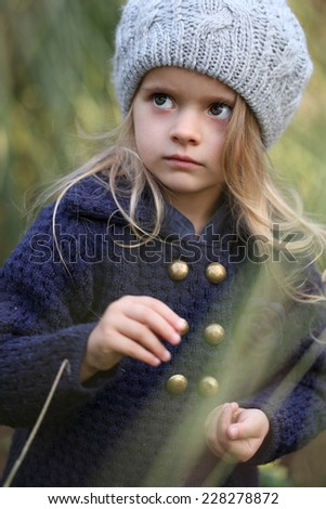 Close-up portrait of adorable smiling child girl wearing knitted hat - stock photo