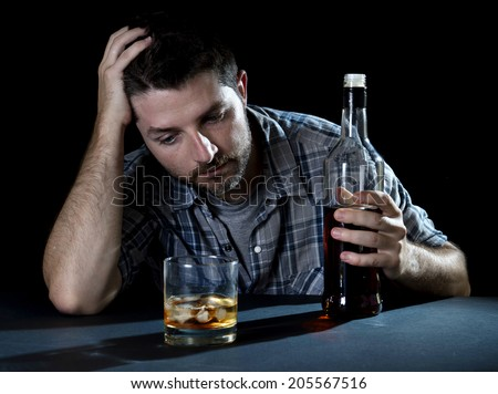 close up portrait of alcoholic wasted man sleeping drunk looking at whiskey glass avoiding temptation thinking of alcohol addiction , drinking abuse , alcoholism concept isolated on black background