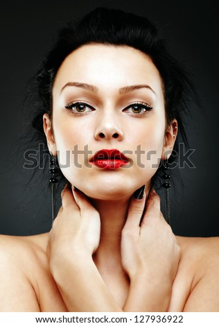 Close-up portrait of alluring woman with her hands around her neck, on gray background. - stock photo
