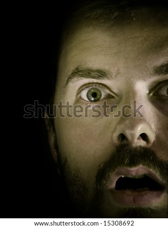 Close-up portrait of amazed guy in the dark - stock photo
