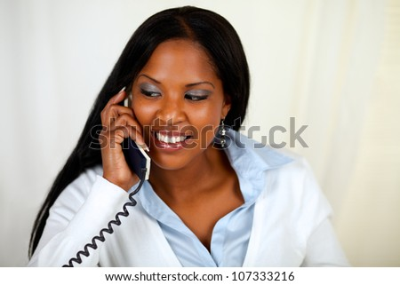 Close up portrait of an african girl conversing on phone at soft colors composition - stock photo