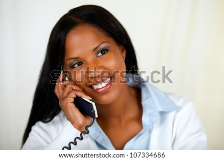 Close up portrait of an african woman conversing on phone at soft colors composition - stock photo