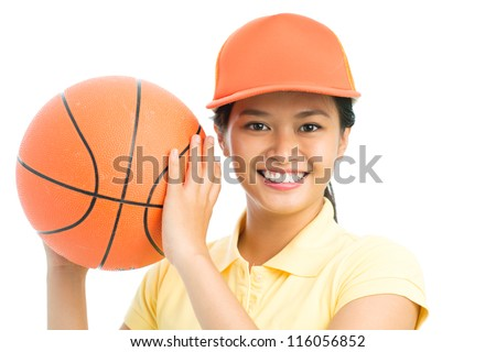 Close-up portrait of an amateur basketball player holding a ball and smiling at camera