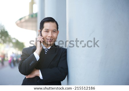 Close up portrait of an asian businessman smiling with cellphone