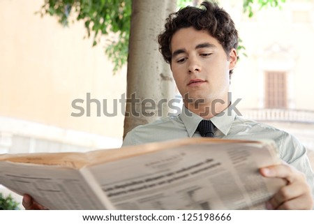 Close up portrait of an aspirational businessman wearing an elegant shirt and tie, reading a financial newspaper in a classic city, outdoors.