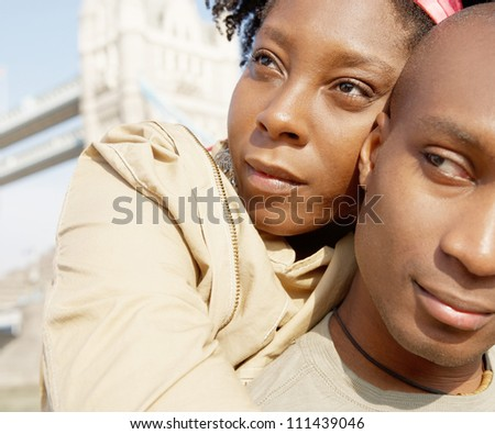 Close up portrait of an attractive african american couple visiting the Tower of London and hugging while on vacation. - stock photo