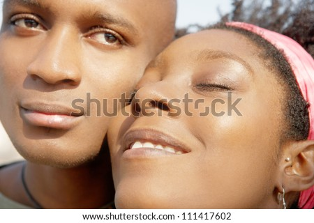 Close up portrait of an attractive african american couple with their heads together, smiling. - stock photo