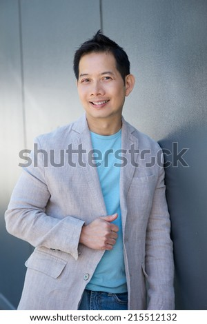 Close up portrait of an attractive asian man smiling outdoors - stock photo