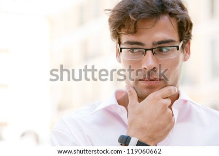 Close up portrait of an attractive businessman being thoughtful while standing next to office buildings in a classic city square. - stock photo