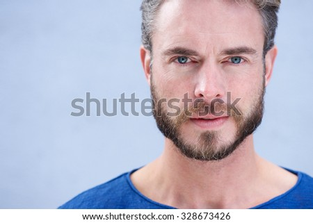 Close up portrait of an attractive man with beard looking at camera - stock photo