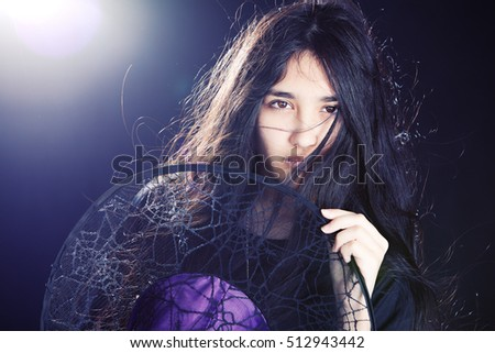 Close up portrait of an attractive mixed race teen, hair blowing across her face and holding a witch's hat.  Background light and lens flare included in image.