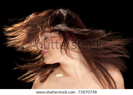 Close-up portrait of an attractive model waving her hair isolated on black