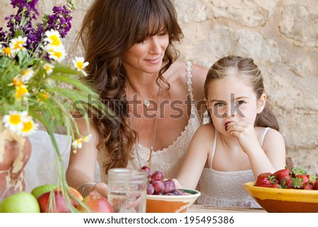 Close up portrait of an attractive mother and young daughter sitting together at a holiday home table outdoors eating fresh fruits and enjoying a summer vacation. Family fun and lifestyle. - stock photo