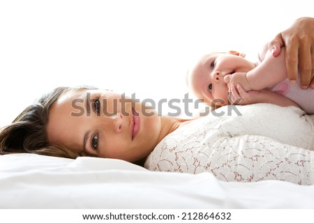 Close up portrait of an attractive mother lying in bed with newborn baby - stock photo