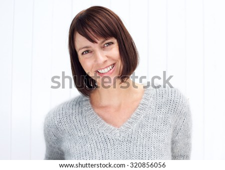 Close up portrait of an attractive older woman smiling against white background - stock photo