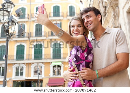 Close up portrait of an attractive romantic young couple relaxing and taking a selfie picture of themselves while visiting a destination city on holiday, together outdoors. Technology lifestyle. - stock photo