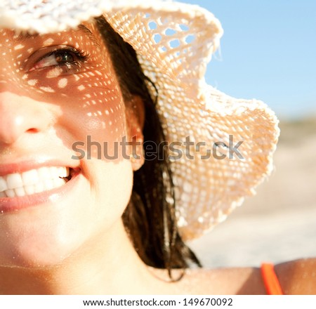 Close up portrait of an attractive smiling woman on vacation on a beach, wearing a straw hat and shading her face with it creating a sun pattern on her skin. Protecting from sun rays.
