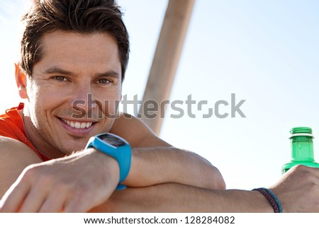 Close up portrait of an attractive sports man sitting on a wooden bench against a blue sky background, holding a bottle of mineral water, smiling. - stock photo