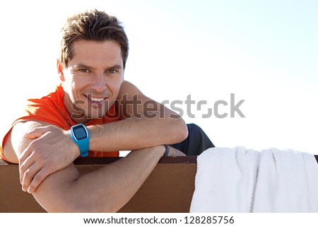 Close up portrait of an attractive sports man sitting on a wooden bench and leaning on his arms against a blue sky background, smiling. - stock photo