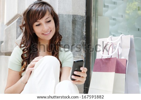 Close up portrait of an attractive teenager woman networking and using her smartphone while sitting and taking a break by a store display window during a shopping day out, outdoors.