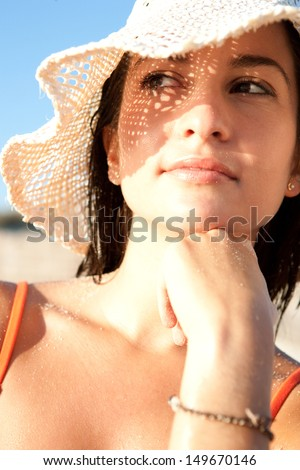 Close up portrait of an attractive woman on vacation on a beach, wearing a straw beam hat and shading her face with it creating a sun pattern on her skin. Protecting from sun rays. - stock photo