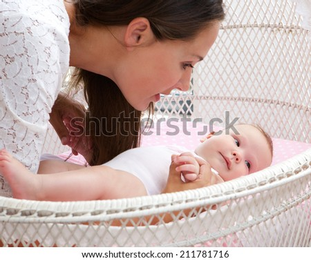 Close up portrait of an attractive woman with baby in cot - stock photo