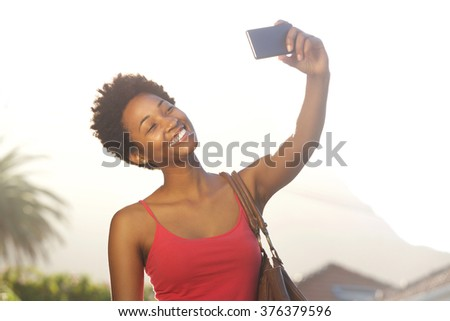 Close up portrait of an attractive young african american woman taking a selfie with her mobile phone  - stock photo
