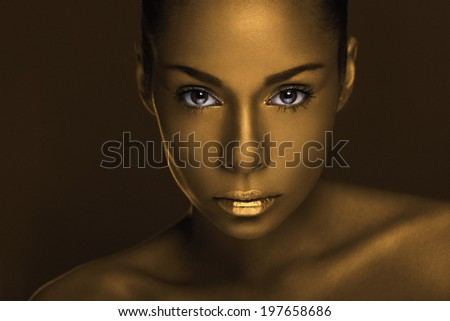 Close up portrait of an attractive young African woman with unique golden makeup. Noise added in post-production.  - stock photo