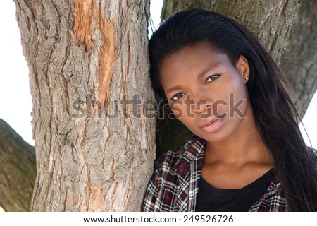 Close up portrait of an attractive young black woman with long hair - stock photo