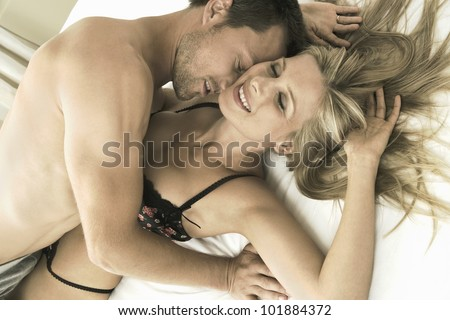 Close up portrait of an attractive young couple kissing in bed, smiling. - stock photo