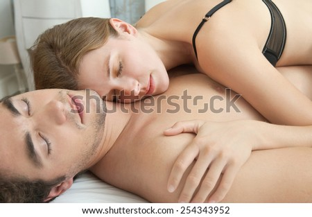 Close up portrait of an attractive young couple sleeping together while hugging on a white linen hotel bed, indoors. Couple and romance living lifestyle. Sensuality and relationships, home interior. - stock photo