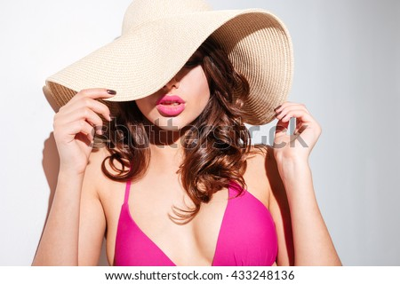 Close-up portrait of an attractive young sexy woman in beach hat isolated on the white background - stock photo