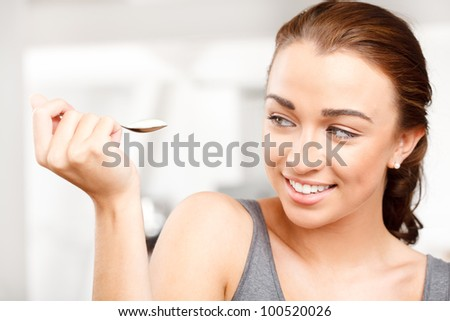 Close-up portrait of an attractive young woman eating yogurt - stock photo