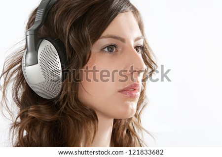 Close up portrait of an attractive young woman focused on listening to music on her headphones, isolated against a white background. - stock photo