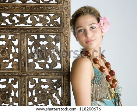 Close up portrait of an attractive young woman wearing an exotic dress and jewelry and leaning on a carved wood screen panel while on vacations at a health spa, smiling.