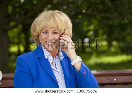 Close up portrait of an elderly beautiful blonde woman talking on a cell phone in a summer park - stock photo